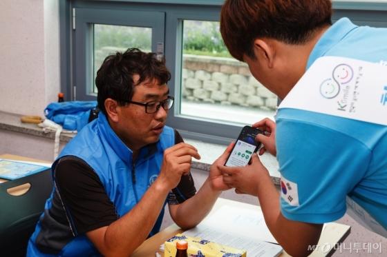 대학생 미소국가대표(오른쪽)가 한 택시기사에게 번역어플 '지니톡' 사용법을 설명하고 있다. /사진제공=한국방문위원회<br />