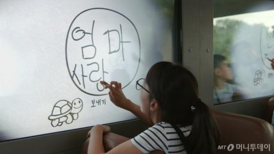 통학버스에 구현된 '스케치북 윈도우' 기술을 이용해 창문에 글을 쓰고 있는 어린이의 모습./사진제공=현대차그룹