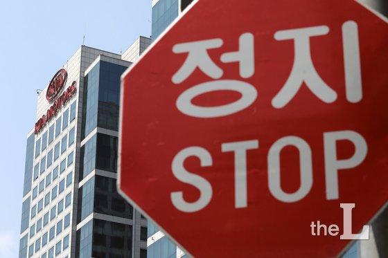 법원이 기아자동차 '통상임금' 사건을 판결한 지난달 31일 서울 서초구에 위치한 기아차 사옥이 교통 표지판 너머로 보이고 있다. 이날 재판부는 근로자들이 청구한 원금 6588억원에 이자 4338억원이 붙은 합계 1조926억원 중 원금 3126억원과 이자 1097억원을 인정한 4223억원의 미지급분을 지급하라고 했다. 이번 소송은 근로자들이 2008년 10월부터 2011년 10월까지 받지 못한 통상임금을 회사에 청구하면서 부터 시작됐다. /사진제공=뉴스1