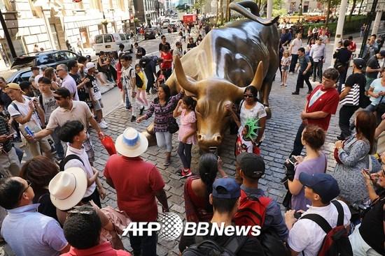 미국 뉴욕증권거래소(NYSE) 앞에 있는 황소상 앞에서 관광객들이 사진을 찍고 있다. 황소상은 강세장(bull market)을 상징한다./AFPBBNews=뉴스1