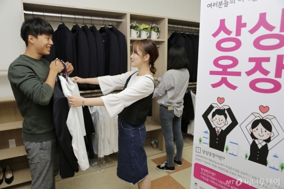 강원대학교에 설치된 '상상옷장'에서 대학생들이 면접용 의상을 입어보고 있는 모습./사진제공=KT&G