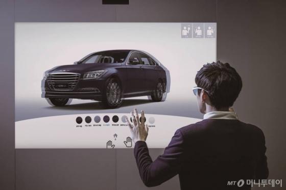 서울시 삼성동 코엑스몰에 위치한 '현대모터스튜디오 디지털'에서 방문객이 제네시스 차량에 디지털로 색깔을 입혀보고 있다./사진=현대차