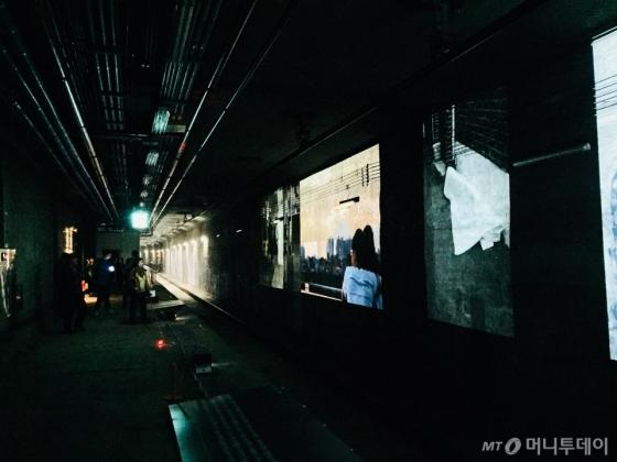 어두운 역 한 쪽엔 사진 작품이 영사되고 있다. /사진=남궁민 기자