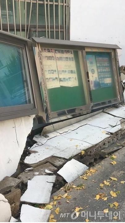 15일 오후 경북 포항시 한 건물 외벽이 지진 충격으로 부서져 내리며 건물 아래에 주차돼있던 승용차를 덮쳤다.  기상청은 이날 오후 2시 29분께 경북 포항시 북구 북쪽 6㎞ 지점에서 규모 5.4 지진이 발생했다고 밝혔다. (독자 제공) /사진=뉴스1