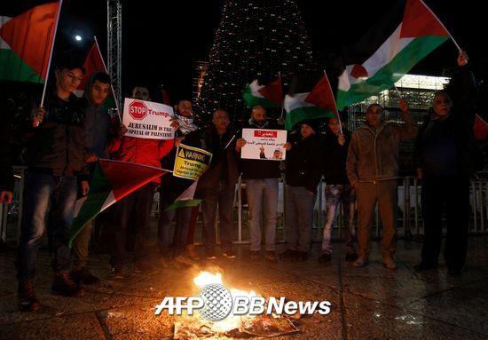도널드 트럼프 미국 대통령이 6일(현지시간) 예루살렘을 이스라엘의 수도로 인정하는 선언을 하자 팔레스타인 주민들이 베들레헴에서 트럼프 대통령의 사진이 든 포스터를 불태우며 시위를 벌이고 있다./AFPBBNews=뉴스1