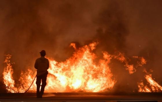 7일(현지시간) 미국 캘리포니아 벤투라 카운티 101번 고속도로 인근에서 소방관이 불을 끄고 있다. /AFPBBNews=뉴스1