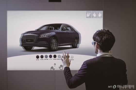 '현대모터스튜디오 디지털' 내 대형 스크린에서 고객이 차량과 색상 등을 선택해 '나만의 차량'을 만들어보고 있다./사진제공=현대차