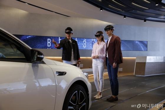 '비트(BEAT) 360'에서 세계 최초로 홀로 렌즈 매개 현실(MR) 기술을 활용해 차량의 특장점을 설명하는 '디지털 도슨트 투어' 프로그램을 고객들이 체험하고 있다./사진제공=기아차