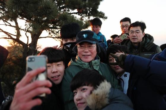 문재인 대통령이 1일 새벽 2018년 새해맞이를 위해 2017년을 빛낸 의인 6명과 함께 북한산에 올라 사모바위에서 일출을 배경으로 기념사진을 찍고 있다./사진=청와대 제공