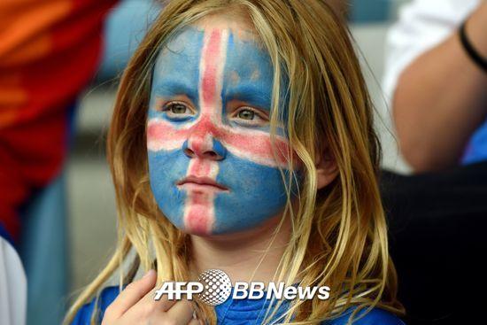 지난해 7월 22일 스위스 두팅햄에서 열린 2017 유럽축구연맹(UEFA) 여자축구선수권 아이슬란드와 스위스 경기에서 얼굴에 아이슬란드 국기를 그려 넣은 한 소녀가 심각한 표정으로 경기를 관람하고 있다./AFPBBNews=뉴스1