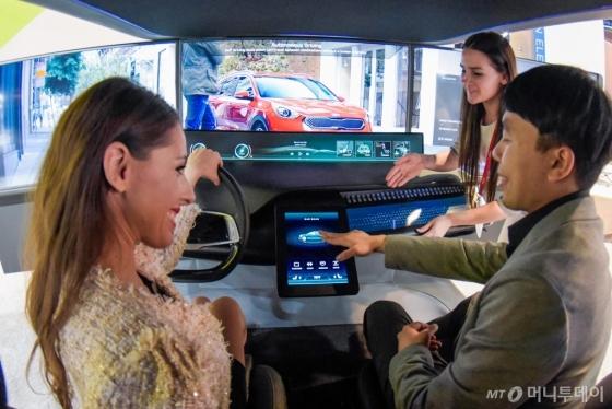 미국 라스베이거스 컨벤션센터 노스(North)홀에 마련된 기아차 전시 부스에서 관람객들이 니로 EV 선행 콘셉트카 내부와 동일한 디자인의 'HMI 칵핏'을 체험하고 있는 모습. /사진제공=기아자동차