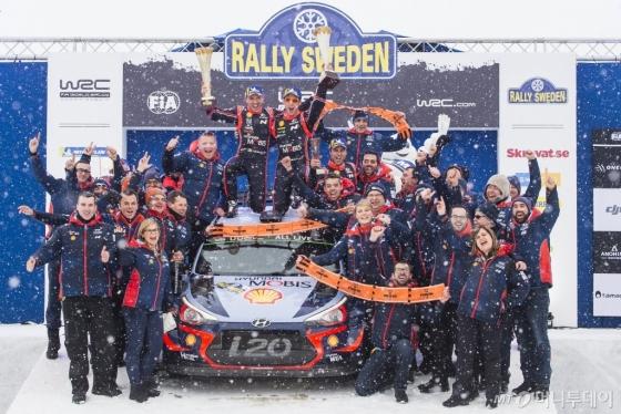 2018 WRC 스웨덴 랠리에서 우승을 차지한 현대 월드랠리팀 선수와 관계자들이 시상대에서 기념 사진을 찍고 있다. 팀 소속 니콜라스 질술(왼쪽)과 티에리 누빌(오른쪽)이 신형 i20 랠리카 위에서 우승컵을 들고 환호하고 있다./사진제공=현대차