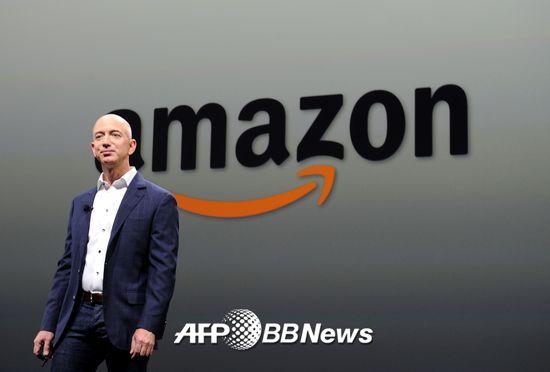 제프 베저스 아마존(amazon) CEO가 회사 로고 앞에 서 있다. 2000년부터 아마존은 현재의 로고를 쓰고 있다. A부터 Z까지 모든 것을 판다는 것과 고객의 웃음을 나타낸다.  /AFPBBNews=뉴스1