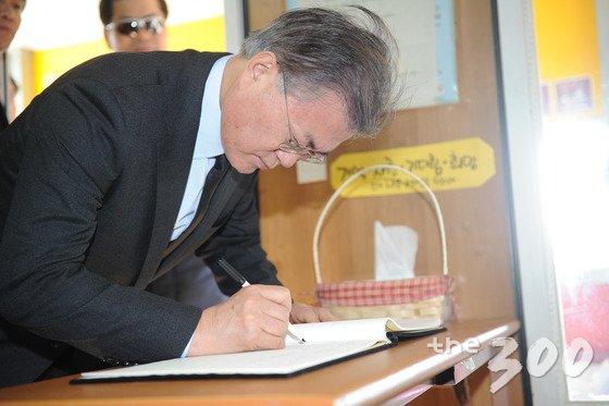 문재인 더불어민주당 전 대표가 2017년 3월10일 박근혜 대통령 탄핵 직후 세월호 미수습자 가족이 있는 전남 진도 팽목항을 방문해 분향소 참배 후 방명록을 쓰고 있다. /사진=뉴스1