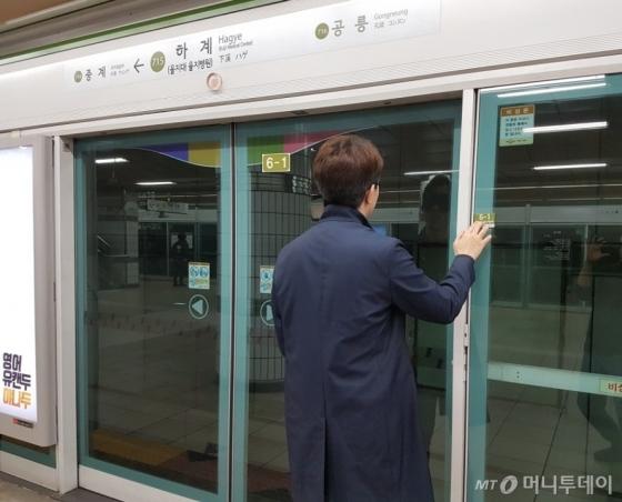 지하철 스크린도어에 설치된 점자를 읽으며 방향과 지하철 칸 등을 파악하고 있다. /사진=유승목 기자