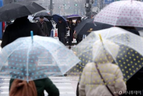 전국 곳곳에 눈, 비가 내리는 오후 서울 광화문 네거리에서 시민들이 우산을 쓴 채 발걸음을 재촉하고 있다.