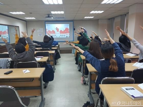 지난 15일 오전서울수화전문교육원 수어 입문반 수업 도중 강사와 수강생들이 아픈 팔을 풀기 위해 막간 체조를 하고 있다. /사진=이재은 기자