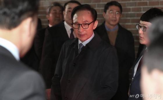 이명박 전 대통령이 22일 구속영장이 발부된 후 구치소 호송을 위해 나온 검찰차량으로 이동하고 있다. /사진=이동훈