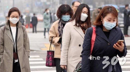 초미세먼지주의보가 발령된 26일 오전 서울 광화문네거리에 시민들이 마스크를 쓴 채 발걸음을 옮기고 있다.