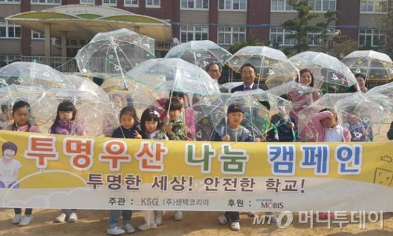 센텍코리아 박식순 회장(오른쪽)과 정왕초 나익주(왼쪽) 교장이 학생들과 '투명우산 나눔 캠페인'을 전개하고 있다./사진제공=센텍코리아