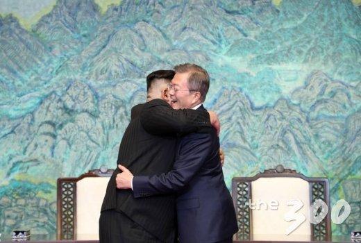 문재인 대통령과 김정은 국무위원장이 평화의 집 1층에서 공동선언문에 서명 후 포옹을 하고 있다.