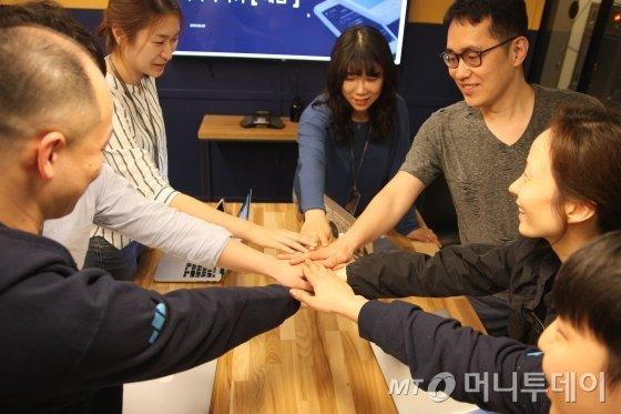 이지혜 대표(오른쪽 두번째)를 포함한 에임의 임직원들이 손을 모아 화이팅을 하고 있다./사진=김유경 기자