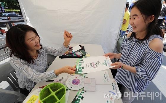 26일 오후 서울 중구 청계광장에서 열린 너와 내가 함께 만드는 스마트 세상 '2018 u클린 청소년 문화마당'에서 '당신의 꿈을 응원합니다' 캘리그라퍼 부스를 찾은 한 아이가 응원을 받고 있다/사진=이기범 기자
