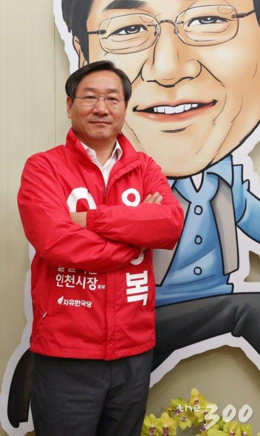 유정복 자유한국당 인천시장 후보가 28일 오전 선거 사무실에 걸려 있는 본인의 캐리커쳐 앞에서 포즈를 취하고 있다. /사진=김휘선 기자