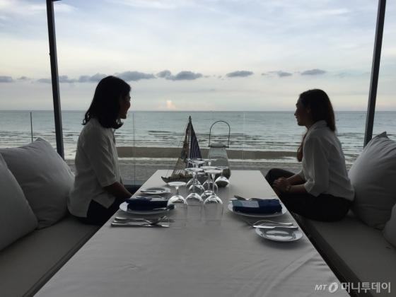 후아힌 매리어트 호텔에서 석양을 배경으로 식사하러 온 여성 여행객. 바다와 인접한 레스토랑은 매리어트 호텔의 가장 큰 장점 중 하나다. /후아힌(태국)=김고금평 기자<br />