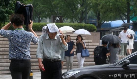서울 청계천 앞을 지나는 시민들이 갑자기 내리는 소나기에 발걸음을 재촉하고 있다./사진=머니투데이