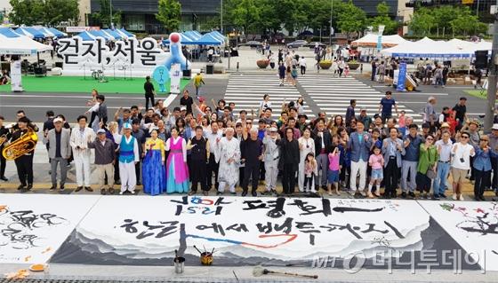 10일 오후 서울 종로구 세종문화회관 야외무대서 진행된 '평화맞이 예술마당' 공연에 참여한 예술가와 관람객들이 함께 단체 사진을 촬영하고 있다./사진=배영윤 기자
