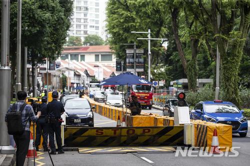 【싱가포르=AP/뉴시스】도널드 트럼프 미 대통령과 김정은 북한 국무위원장 간 첫 정상회담이 열리는 싱가포르에서 10일 김 위원장이 묵을 세인트 레지스 호텔 인근 도로들이 차단된 가운데 경찰들이 경계를 서고 있다. 2018.6.10   <저작권자ⓒ 공감언론 뉴시스통신사. 무단전재-재배포 금지.>