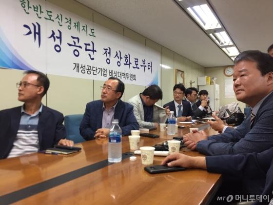 개성공단입주기업인들이 12일 서울 영등포구 여의도 개성공단기업협회 사무실에서 북미 정상회담을 TV 중계로 보고 있다.