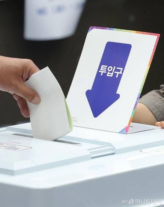 제7회 전국 동시 지방선거 및 교육감 선거, 국회의원 재·보궐 선거일인 13일 오전 서울 은평구 진관동 주민센터에 마련된 투표소에서 한 시민이 투표를 하고 있다.