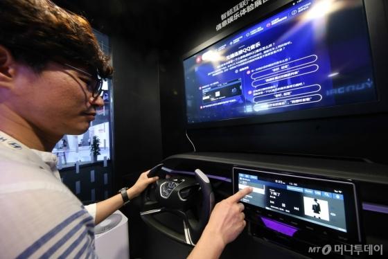 기아차가 13일 중국 상하이 신국제박람중심에서 개막한 'CES ASIA 2018'에서 텐센트 QQ뮤직과 협업해 개발한 중국 전용 인포테인먼트 시스템을 공개했다. 관람객이 새 인포테인먼트 시스템 전시물을 보고 있다./사진=기아차