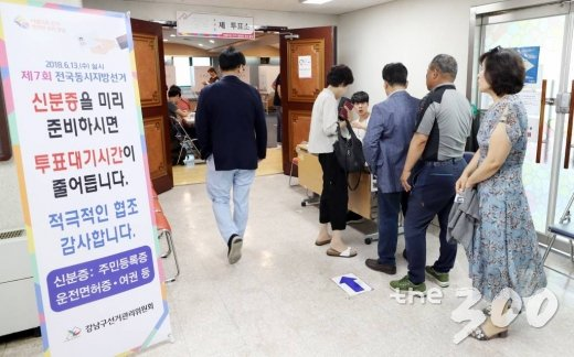 제7회 전국 동시 지방선거 및 교육감 선거, 국회의원 재·보궐 선거일인 13일 서울 강남구 청담동 주민센터에 마련된 투표소에서 유권자들이 줄지어 서 있다.