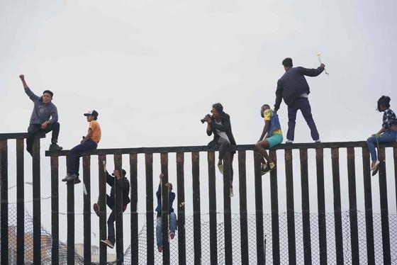 중미 캐러밴 난민들이 29일(현지시각) 美-멕시코 국경도시인 캘리포니아 주 산 이시드로의 장벽에 올라가 입국허용을 요구하는 시위를 하고 있다. 미국 정부는 국경지대의 이민자들에 대한 체포 가능성까지 거론하면서 불법 입국에 대해 강하게 경고하고 나섰다. /AFP=뉴스1