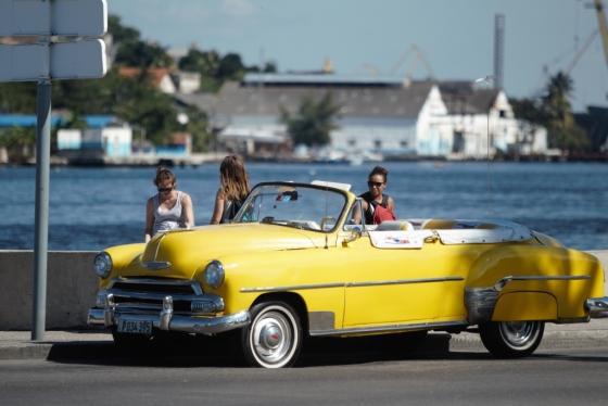 클래식카를 타고 가다 말레콘에 차를 세운 관광객들.