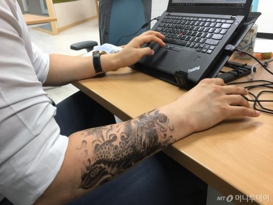 5일 오전 용무늬 타투 스티커로 타투를 한 뒤 출근한 기자가 책상에 앉아 일하고 있다./사진=남형도 기자
