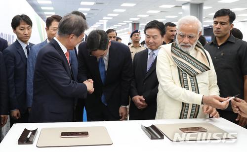 【뉴델리(인도)=뉴시스】박진희 기자 = 문재인 대통령은 9일(현지시간) 나렌드라 모디 (Narendra Modi) 인도 총리와 함께 인도 뉴델리 인근 노이다 공단에서 개최된 '삼성전자 제2공장 준공식'에 참석하여 이재용 삼성전자 부회장 안내로 신규 생산라인을 둘러보고 있다. 2018.07.09.   pak7130@newsis.com