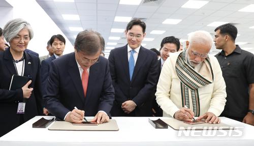 【뉴델리(인도)=뉴시스】박진희 기자 = 문재인 대통령은 9일(현지시간) 나렌드라 모디 (Narendra Modi) 인도 총리와 함께 인도 뉴델리 인근 노이다 공단에서 개최된 '삼성전자 제2공장 준공식'에 참석하여 신규라인에서 생산된 휴대폰에 서명을 하고 있다. 2018.07.09.   pak7130@newsis.com