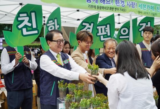 친환경 편의점 그린 세븐 캠페인에 참석한 정승인(왼쪽) 세븐일레븐 대표와 모델 토니안이 일회용 무지컵을 화분으로 재활용한 기능성 식물을 시민들에게 나눠주고 있다. /사진제공=코리아세븐