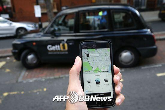 한 소비자가 차량공유서비스 우버를 사용하고 있는 모습./AFPBBNews=뉴스1
