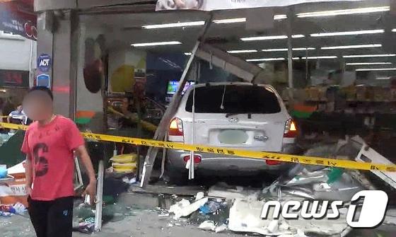 12일 오후 김모씨가 몰던 산타페 차량이 주차된 차량과 보행자를 친 뒤 슈퍼마켓 건물을 들이받고 멈춰섰다. (광진소방서 제공) 2018.7.13/뉴스1