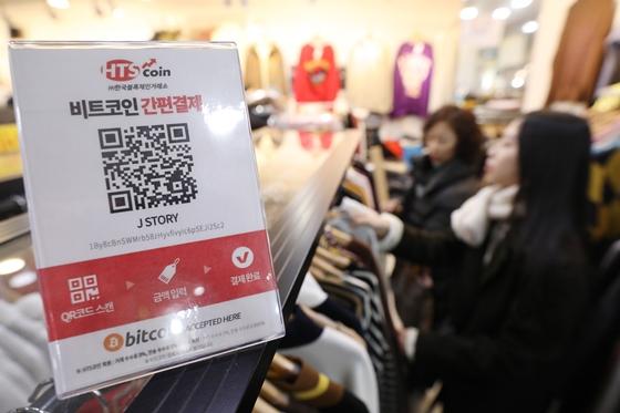 서울 강남고속버스터미널 지하상가 '고투몰'은 HTS코인과 손잡고 지난해 12월 150개 매장에 비트코인 간편결제 서비스를 도입했다. 이를 안내하는 안내 판넬 뒤로 쇼핑객들이 옷을 고르고 있다. /사진=뉴스1.