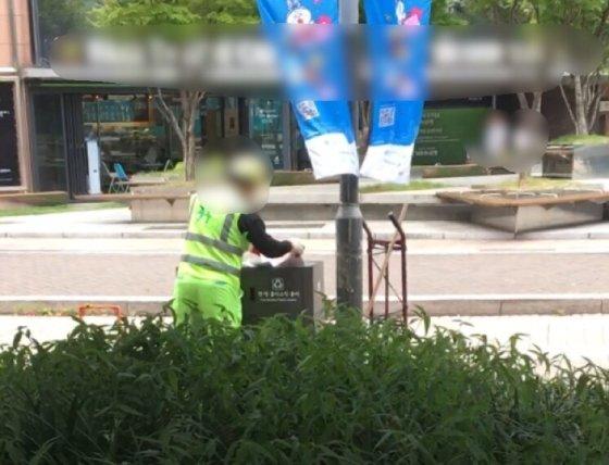 폭염으로 무더운 날씨, 서울 중구 명동서 한 환경미화원이 쓰레기통을 정리하고 있다./사진=남형도 기자