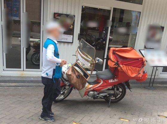 무더운 날씨에 오토바이를 타고 배달을 다니느라 분주해하던 우체국 집배원의 모습./사진=남형도 기자
