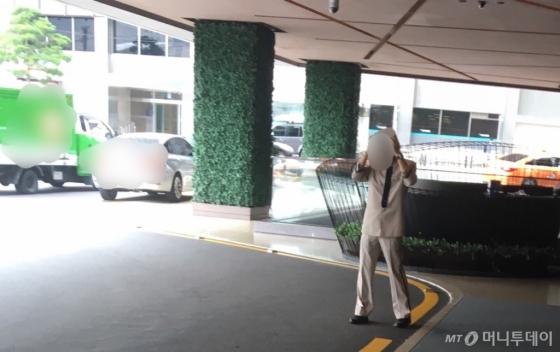 한 호텔 안내직원이 모자를 벗고 땀방울을 훔친 뒤 다시 옷매무새를 정돈하고 있다./사진=남형도 기자