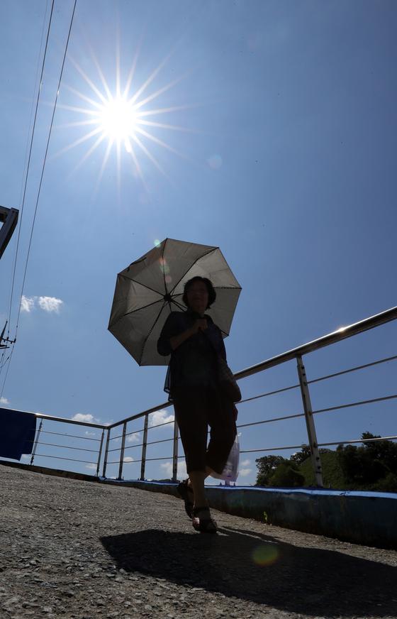 무더위가 이어지던 지난 2일 전북 전주시 남부시장 근처에서 양산으로 햇볕을 피한 한 시민의 모습/사진=뉴스1