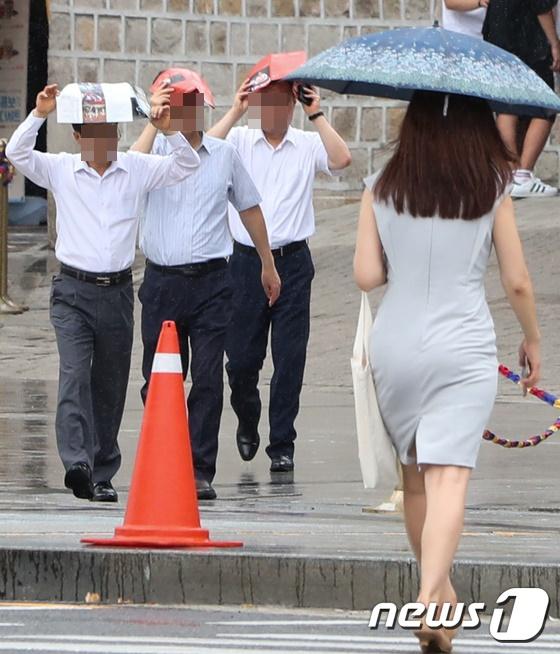 9일 서울시청 인근에서 시민이 내리는 비를 맞으며 발걸음을 재촉하고 있다. /사진= 뉴스1